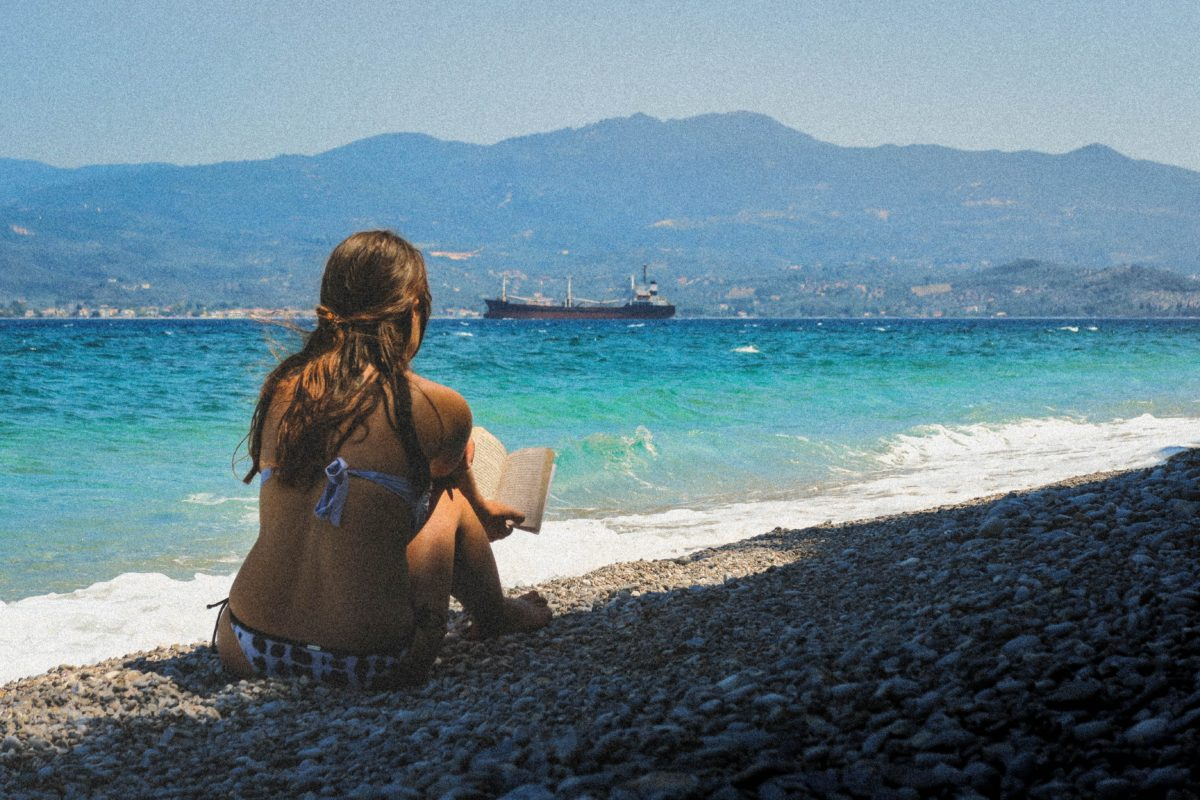 Woman in a bikini sitting on a pebble beach reading a book at Glifa, Greece